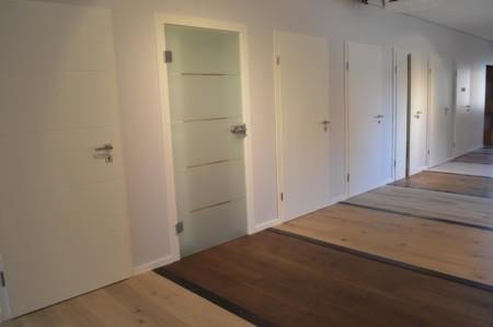 Glastüren und weiße Holztüren mit unterschiedlichen Bodenbelägen